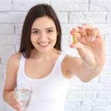 ženska s kapsulo naravnega prehranskega dopolnila Germa